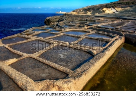 Manmade salt pools on a Gozo coastline - stock photo