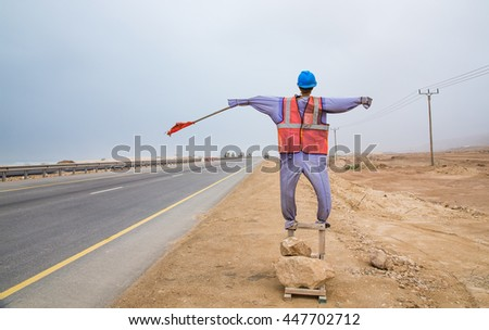 mannequin dressed in safey clothing with a red warning flag standing on the side of the road in Salalah Oman