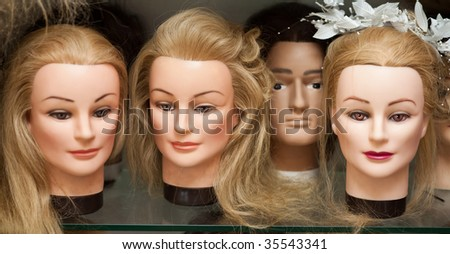 Mannequin heads with wigs in a hairdressing salon - stock photo