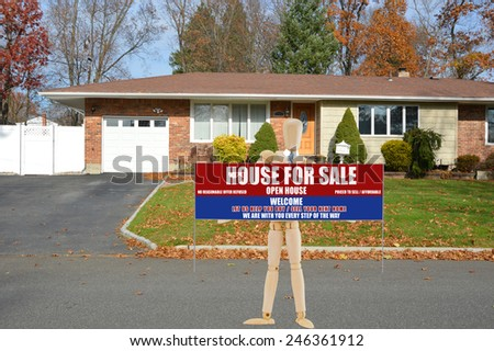 Mannequin holding Real estate for sale open house welcome sign suburban brick ranch style home white picket fence blacktop driveway autumn blue sky day residential neighborhood USA - stock photo