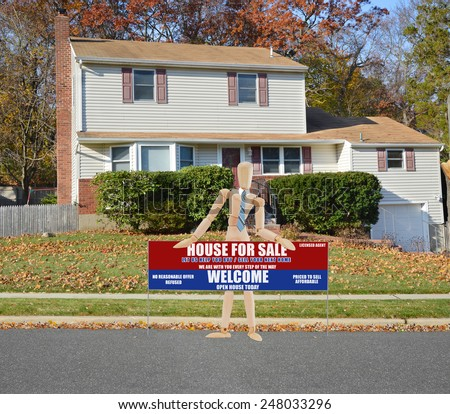 Mannequin holding Real estate for sale open house welcome sign Suburban Tan High Ranch home with leaves on front lawn autumn day residential neighborhood Sunny blue sky