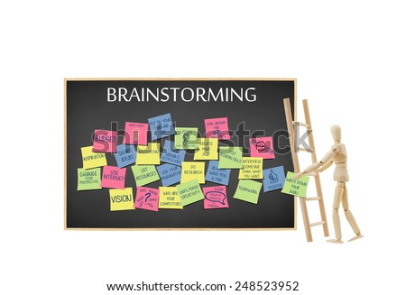 Mannequin holding (write down your goals) written on post it note climbing ladder to add to blackboard filled with Brainstorming ideas isolated on white background - stock photo