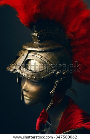 Mannequin in helmet with red feathers on black background
