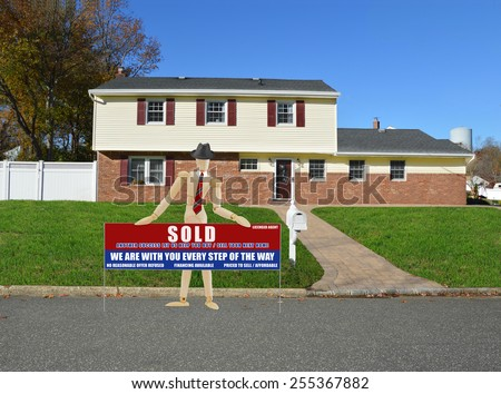 Mannequin wearing red striped tie and black hat holding real estate sold (another success let us help you buy sell your next home) sign suburban home sunny clear blue sky residential neighborhood USA - stock photo