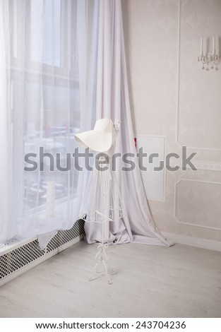 Mannequin with women's hat inside white room - stock photo