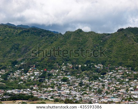 Manoa Valley on the Island of Oahu.  Featuring Mountains, houses, school and graveyard. - stock photo