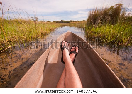 mans feet relaxing a canoe with an interesting point of view - stock photo