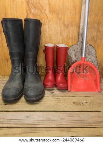 mans green rubber boots and childs red rubber boots in a shed with tools father and son concept - stock photo