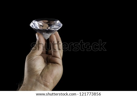 Mans hand holding a large fake diamond against black background