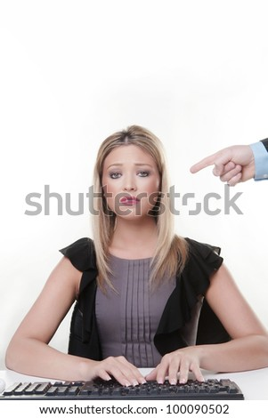 mans hand pointing at a young woman working at her desk she not looking to happy has she done something wrong
