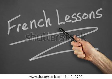 Mans hand pointing to a french lessons message on a chalkboard.