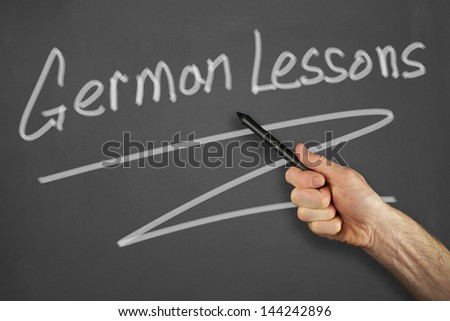 Mans hand pointing to a german lessons message on a chalkboard.