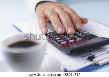 Mans hand working with a calculator at his desk analysing statistics with a cup of coffee in the foreground, close up view