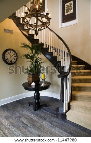 Mansion hallway with winding staircase and luxurious decor. - stock photo