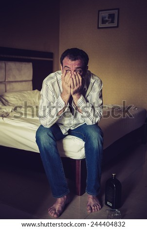 Mansitting on the bed with headache depression and hangover. LOMO effect  - stock photo