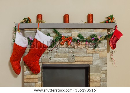 Mantelpiece decorated with Christmas candles, socks, pine tree branches, garland and ribbons above fireplace.