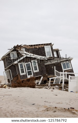 MANTOLOKING, NJ - JAN 13: A tilted house off its foundation on the beach on January 13, 2013 in Mantoloking, New Jersey. Clean up continues 75 days after Hurricane Sandy struck in October 2012. - stock photo
