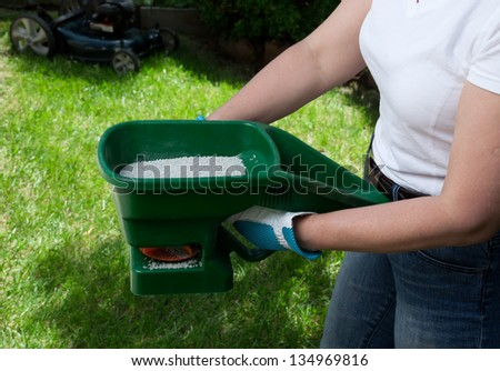 Manual fertilizing of the lawn in back yard in spring time - stock photo