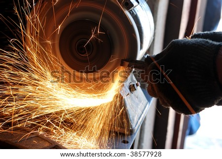 Manual sharpening of a tool on grinding machine - stock photo