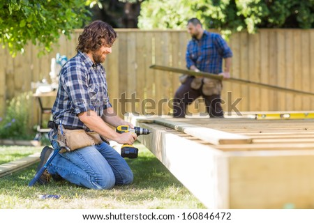 Manual worker drilling wood with coworker working in background at construction site - stock photo