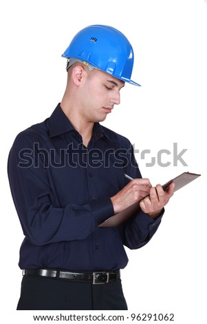 Manual worker filling up a clipboard. - stock photo