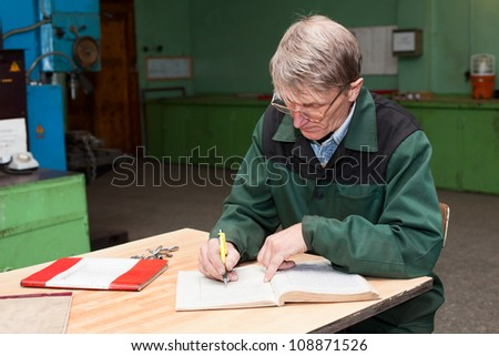 Manual worker fills the journal in the workplace. Copyspace - stock photo