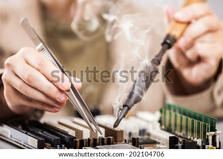 Manual worker human hand holding soldering iron tool repairing computer electronics circuit board - stock photo