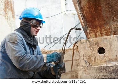 manual worker in protective work wear  welding by gas torch - stock photo