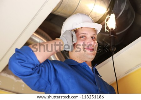 Manual worker inspecting air-conditioning system - stock photo