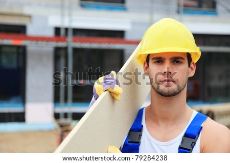 Manual worker on construction site carrying wooden board. - stock photo