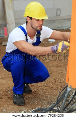 Manual worker on construction site checking power connection. - stock photo