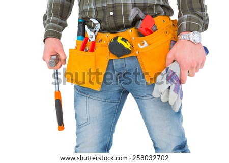 Manual worker wearing tool belt while holding gloves and hammer on white background