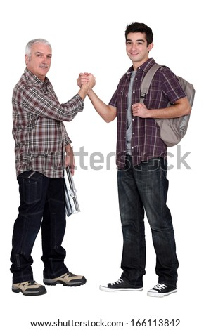 Manual worker welcoming intern - stock photo