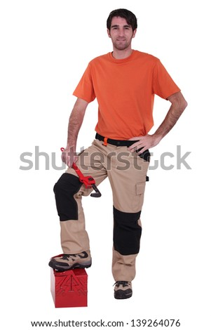 Manual worker with foot on tool-box - stock photo