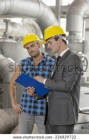 Manual worker with supervisor discussing over clipboard in industry - stock photo