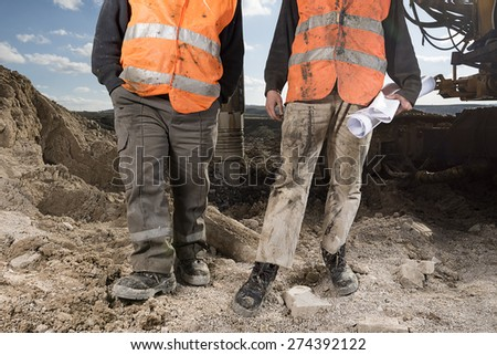 Manual workers at construction site - stock photo