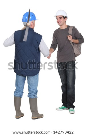 Manual workers shaking hands - stock photo