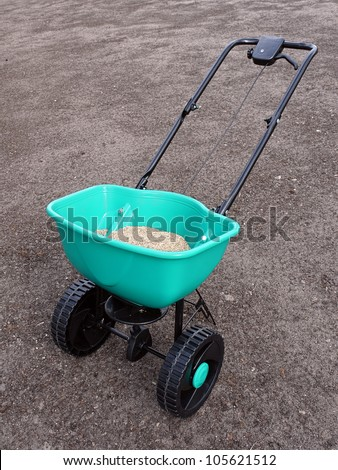 Manually operated seeder filled with grass seeds shot on soil - stock photo