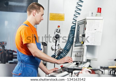 manufacture technician worker near cnc milling machine center at tool workshop - stock photo