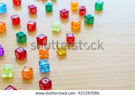 Many abc education cube scattered on wooden table. - stock photo