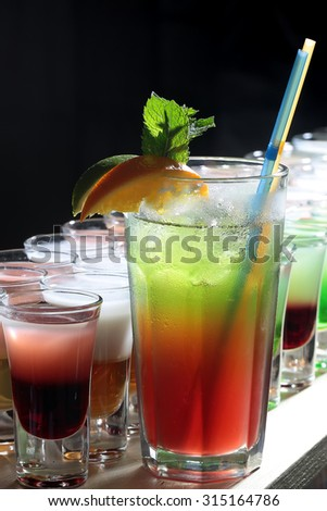 Many alcoholic tasty hard shot cocktails in drinking glasses and one long beverage with straws and orange green brown red and white colors standing in row on black studio background, vertical picture - stock photo