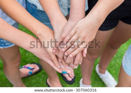Many arms of girls with hands on top of each other above green grass - stock photo