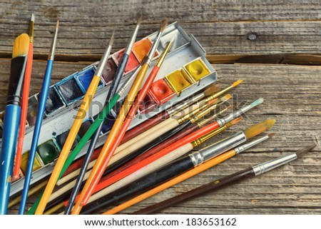 Many artist brushes for use with any media like acrylic, watercolor and others with professional set of watercolor paints - stock photo