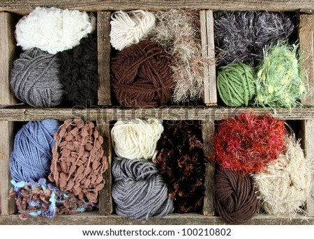 many autumn colored yarn balls in an aged wooden box - stock photo