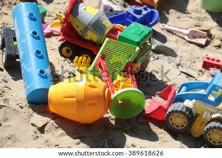 Many beautiful childish plastic multicolored toys car lorry small rake on sand background in summer playtime boyish activity closeup, vertical picture  - stock photo