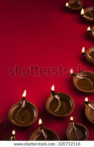 many beautiful diwali diya together on a red background, diwali greeting - stock photo