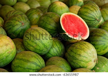 Many big sweet green watermelons and one cut watermelon - stock photo