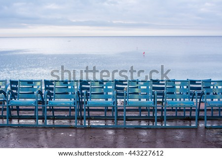 Many blue chairs facing the Mediterranean sea at the Promenade des Anglais, Nice, France. Panoramic view of Chairs near the ocean on the French Riviera in Nice, France - stock photo