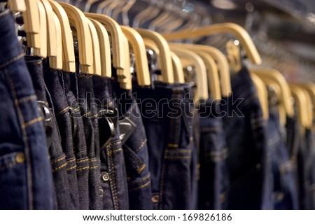 Many blue denim jeans on coat hanger - stock photo