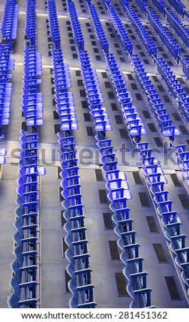 many blue seats in the stands before the sporting event